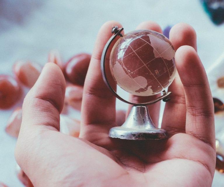 hand holding globe Jeenie interpreters wherever you need them